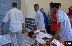 Somalis help a wounded civilian at a hospital following a mortar attack in Mogadishu, Feb. 25, 2016, following a mortar attack near Somalia's presidential palace that killed four people and injured several others.