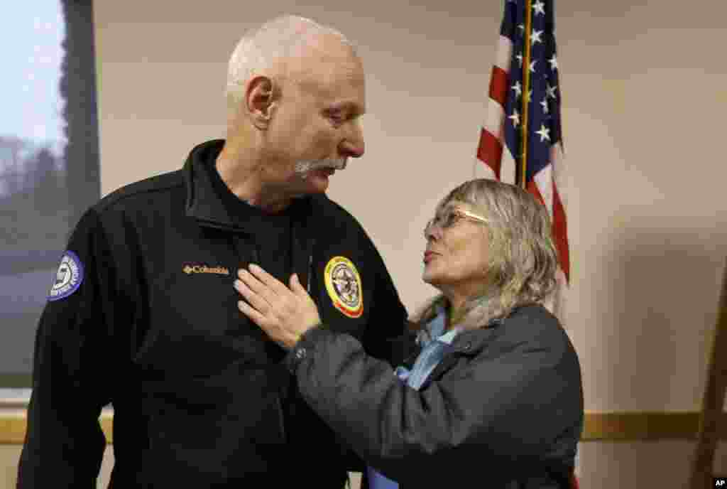Robin Youngblood, right, smiles after embracing Snohomish County helicopter crew chief Randy Fay, who helped rescue her from the scene of a deadly mudslide days earlier, March 26, 2014, in Arlington, Washington.