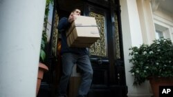 A removals worker carries a box out of the residential annex of the Iranian embassy in central London December 2, 2011.