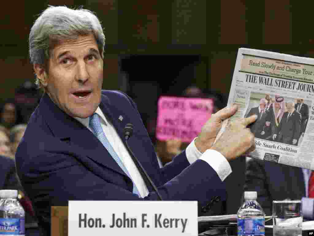 Secretary of State John Kerry points to a newspaper photo of the recent Arab summit in Saudi Arabia as an example of the kind of coalition he expects in combating Islamic State extremists in Iraq and Syria, on Capitol Hill in Washington, Sept. 17, 2014.