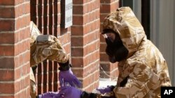 Specialist team members in military protective suits use a jar in the front doorway as they search the fenced-off John Baker House for homeless people on Rollestone Street in Salisbury, England, July 6, 2018. British police are scouring sections of Salisb