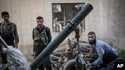 Anggota Tentara Pembebasan Suriah mengisi tabung mortir dalam pertempuran di desa Kafr Nboudah, provinsi Idlib, Suriah utara. (Foto: AP)
