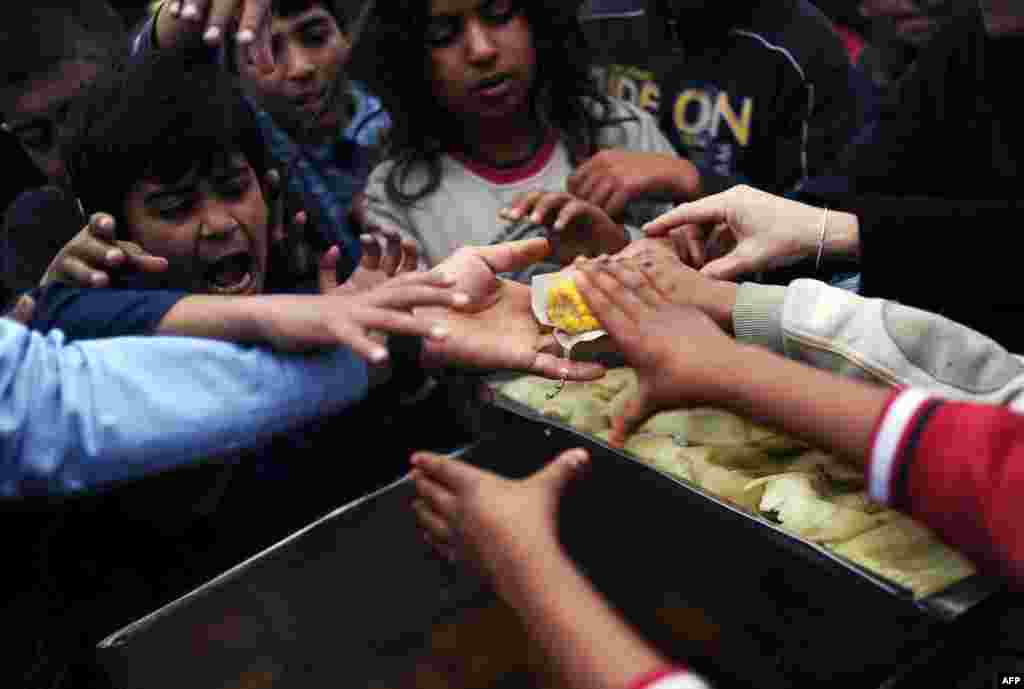 Syrian refugees try to grab food in a park, in Istanbul, Turkey.