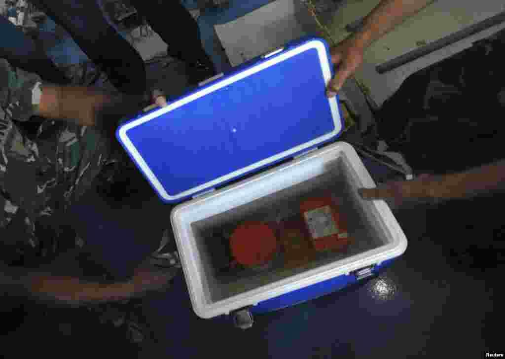Tentara Indonesia memperlihatkan alat perekam suara kokpit AirAsia 8501 di atas dek kapal KRI Banda Aceh di Laut Jawa (13/1).