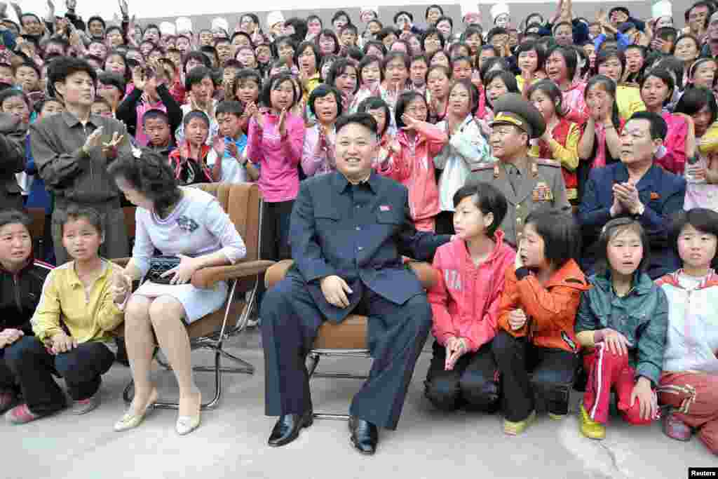 North Korean leader Kim Jong-un (C) and his wife Ri Sol-ju during a visit to the Pyongyang Myohyangsan Children's Camp situated at the foot of Mt. Myohyang in North Phyongan Province, in this photo released by North Korea's Korean Central News Agency (KCNA)