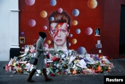 A woman looks at a mural of David Bowie in Brixton, south London, Britain, Jan. 12, 2016. Sales of David Bowie's last album - released two days before his death from cancer - have soared along with downloads of his greatest hits.