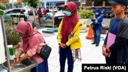 Sejumlah warga mencuci tangan di wastafel portable yang dibangun Pemkot Surabaya (Foto: VOA/ Petrus Riski).