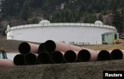 FILE - Replacement pipe is stored near crude oil storage tanks at Kinder Morgan's Trans Mountain pipeline terminal in Kamloops, British Columbia, Canada, Nov. 15, 2016.