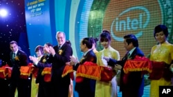 In this file photo, Intel's Paul Otellini, center, and Vietnam's official Le Thanh Hai, fourth right, at open the assembly and test facility of Intel's chipset products at Saigon High Tech Park, October 29, 2010. (AP Photo/Le Quang Nhat)