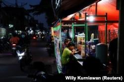 Orang-orang makan malam di tenda jajanan kaki lima saat pelonggaran PPKM di tengah pandemi COVID-19, di Jakarta, 28 Juli 2021. (Foto: REUTERS/Willy Kurniawan)