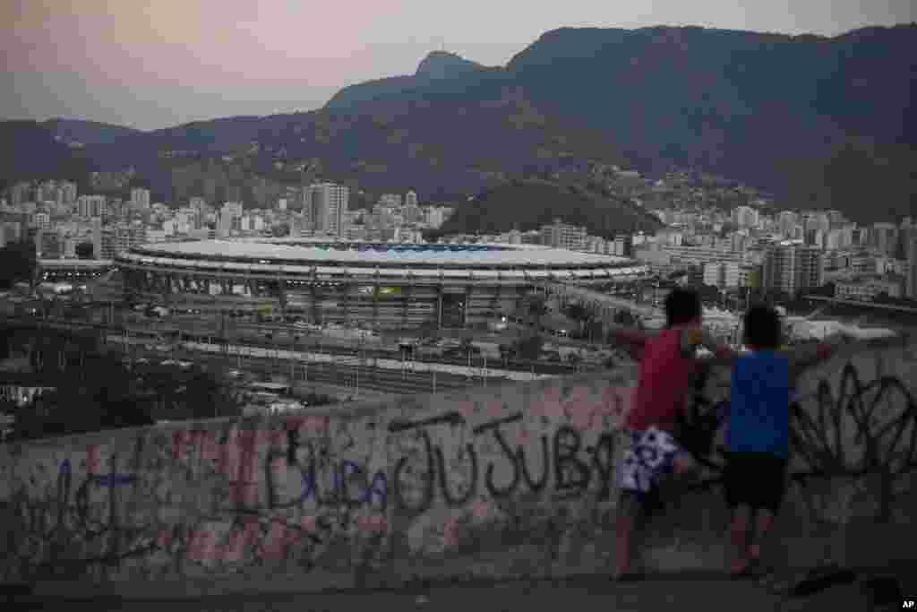 Deux garçons regardent de loin le Stade Maracaña, à partir des bidonvilles de Mangueira, avant l'ouverture des Jeux olympiques de 2016 d'été à Rio de Janeiro, 5 août 2016.