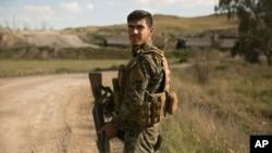 Seorang tentara Pasukan Demokratik Suriah berjaga saat truk-truk yang membawa anggot kelompok militan ISIS dan keluarganya menyerah di Baghuz, Suriah, dan pindah ke kamp, 19 Maret 2019.
