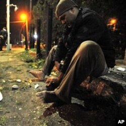 Illegal immigrant cleans his shoes in the square after crossing the border with Turkey in Nea Vissa, northeastern Greece, 480 kilometers east of Thessaloniki (File Photo)