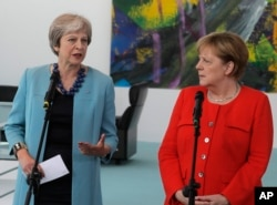 FILE - German Chancellor Angela Merkel, right, and British Prime Minister Theresa May give statements prior to a meeting in the chancellery in Berlin, Germany, July 5, 2018.