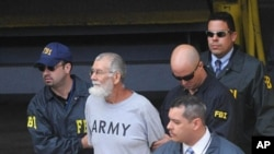 Norberto Gonzalez Claudio, 65, is being escorted by FBI agents after his court appearance in San Juan, Puerto Rico, May 10, 2011
