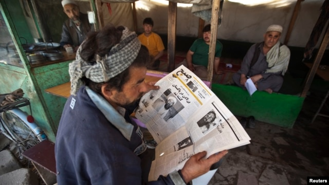 An Afghan man reads a newspaper at a tea shop in Kabul in this May 3, 2011, file photo.