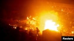 香港理工大学的抗议者站在燃烧的大火旁。(2019年11月18日)