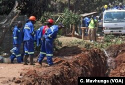 Workers try to unblock a sewer pipe in Harare, Zimbabwe, Sept. 11, 2018, which residents say has been like that for at least three months.