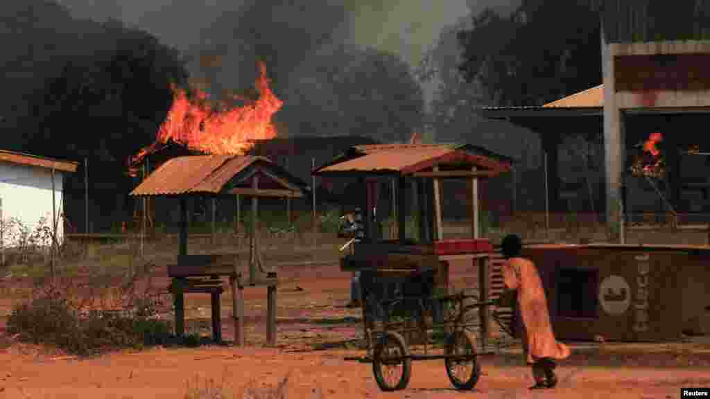 A girl pushes a hand cart past burning houses in Bossangoa, north of Bangui, Jan. 2, 2014.