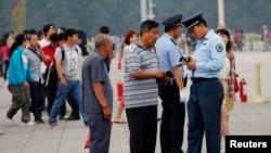 Nhân viên an ninh kiểm tra thẻ căn cước của du khách tại Quảng trường Thiên An Môn ở Bắc Kinh, ngày 4/6/2013.