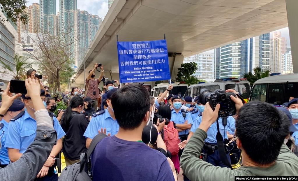 大批在场戒备的警员多次向西九法院大楼外排队的市民高举蓝旗及紫旗,警告聚集的市民涉嫌非法集结,高呼的口号涉嫌违反国安法 (美国之音/汤惠芸)(photo:VOA)
