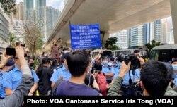 大批在场戒备的警员多次向西九法院大楼外排队的市民高举蓝旗及紫旗,警告聚集的市民涉嫌非法集结,高呼的口号涉嫌违反国安法 (美国之音/汤惠芸)