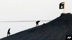 Extremistas del Estado Islámico izan la bandera del grupo terrorista cerca de la frontera entre Siria y Turquía.