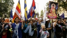 Villagers from Boeung Kak lake march through the main street, wearing a portrait of detained Yoam Bopha, Buddhism, poster and flags to mark the World Women's Day in Phnom Penh, Cambodia, Friday, March. 8, 2013. Bopha was arrested by local authorities after her protest over compensation for her loss of her house due to a new luxury housing development. The protesters demanded the release of Bopha. (AP Photo/Heng Sinith)