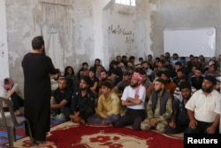 FILE - Rebel fighters from the Ahrar al-Sham Movement take Islamic and Koran lessons inside a camp, during the holy month of Ramadan in Idlib countryside, Syria, July 7, 2015. The group pulled out of a meeting of opposition groups in Saudi Arabia, Dec. 10