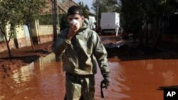 A Hungarian firefighter wearing protective gear walks through a street flooded by toxic red sludge in Devecser, Hungary, 09 Oct 2010