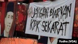 """Seorang warga tengah memasang spanduk bertuliskan pesan agar Presiden """"Jangan Biarkan KPK Sekarat"""" di Solo, 18 Februari 2015 (Foto: VOA/Yudha)."""
