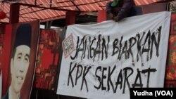 """Seorang warga tengah memasang spanduk bertuliskan pesan agar Presiden """"Jangan Biarkan KPK Sekarat"""" di Solo (foto: dok. VOA/Yudha)."""