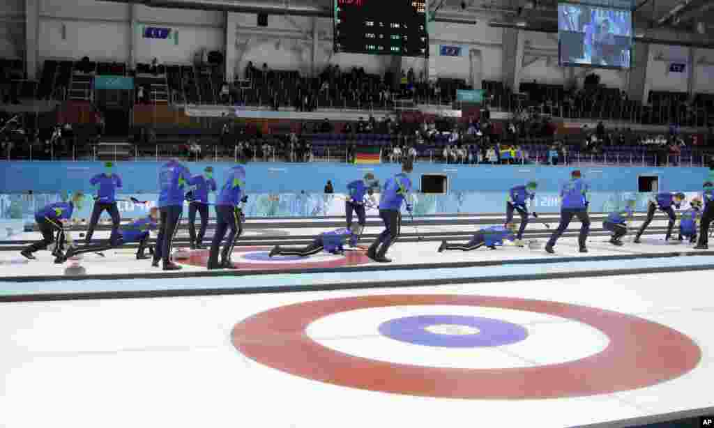 This multiple exposure photo shows the Sweden curling team throwing during a round robin session against China in the Ice Cube Curling Center at the 2014 Winter Olympics, Feb. 14, 2014.