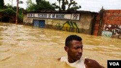 Un hombre trata de cruzar una calle inundada en el poblado de Barlovento, en el venezolano estado de Miranda.