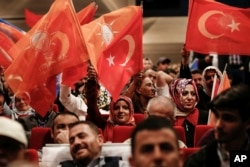 Supporters of Turkey's President and ruling Justice and Development Party leader Recep Tayyip Erdogan wave flags as they listen to him speak during an election rally in Istanbul, Turkey, May 29, 2018.