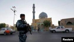 Dalam foto tertanggal 28/7/2014 ini seorang polisi Irak berjaga-jaga di depan sebuah masjid Sunni di Baghdad pada saat perayaan Idul Fitri.