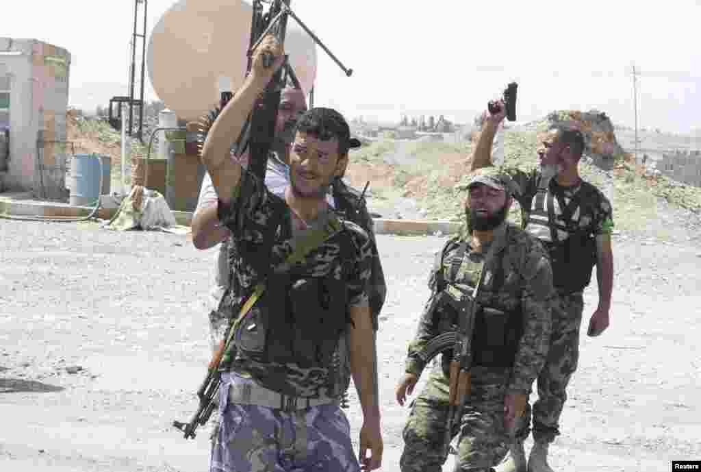 Shi'ite volunteers carry their weapons during an intensive security deployment to fight against militants of the Islamic State, formerly known as the Islamic State of Iraq and the Levant (ISIL), in the town of Tuz Khurmatu, Iraq, Aug. 31, 2014.