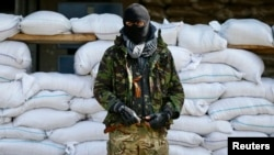 An armed man, who is wearing black and orange ribbons of St. George - a symbol widely associated with pro-Russian protests in Ukraine, stands guard in front of barricades outside the mayor's office in Slovyansk April 18, 2014.
