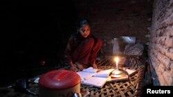 اسلام آباد میں بجلی کی لوڈشیڈنگ کی وجہ سے طالبہ موم بتی کی روشتی میں پڑھ رہی ہے۔ (فائل فوٹو)