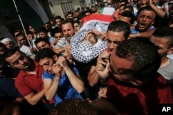 Palestinians carry the body of Mohammed Abu Hashhashi, 17, during his funeral in the West Bank refugee camp Fawwar, near the West Bank city of Hebron, Wednesday, Aug. 17, 2016. Abu Hashhashi was killed by live fire during clashes between Israeli troops and Palestinians the day before.