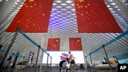 资料照:一名旅客推着行李车从深圳机场悬挂的中国国旗下走过。