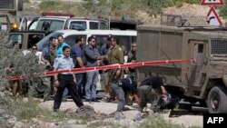 Israeli security forces and forensics surround the body of a Palestinian man, in the West Bank village of Sinjil, who was killed by Israeli forces after injuring two Israelis in a stabbing attack near the entrance to the Shilo settlement on route 60, the main road linking the West Bank cities of Ramallah and Nablus, April 8, 2015.