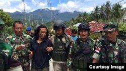 Tentara mengawal Basri, orang penting dalam kelompok Santoso. (Satgas Operasi Tinombala 2016)