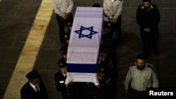 Members of the Knesset guard carry the flag-draped coffin of former Israeli prime minister Ariel Sharon outside the Knesset, Israel's parliament, in Jerusalem Jan. 12, 2014.