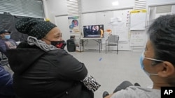 Immigrant worker Blanca Cedillos, center, who is a nanny, glances over at cleaning lady Graciela Uraga, as they watch the presidential inauguration from the Workers Justice Center, a center that supports immigrant workers rights, Wednesday, Jan. 20, 2021