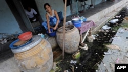 A Burmese migrant washes dishes outside her room at an apartment building housing Burmese migrant workers in Mahachai, an industrial area south of Bangkok, August 25, 2010.