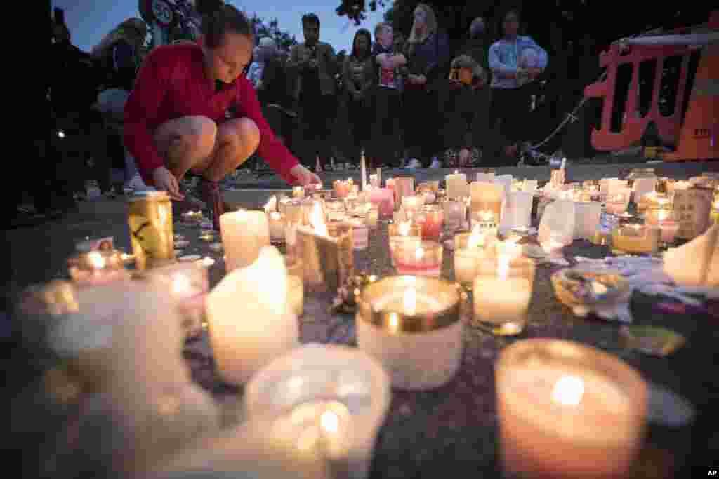 총격사건이 발생한 뉴질랜드 크라이스트처치의 알 누르 이슬람 사원 앞에서 시민이 숨진 희생자들을 애도하기 위해 촛불을 켜고 있다.