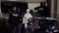 Cảnh sát và các nhà điều tra pháp y đứng bên ngoài tòa soạn tuần báo Charlie Hebdo ở Paris, ngày 7 tháng 1, 2015.