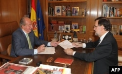 Spain's King Juan Carlos (L) hands over a letter of abdication to Spain's Prime Minister Mariano Rajoy at the Zarzuela Palace in Madrid.