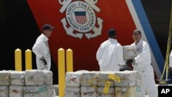 U.S. Coast Guard crew members unload cocaine which was seized from off the coast of Honduras in August. The U.S. is partnering with Honduras to fight drug-related crime.
